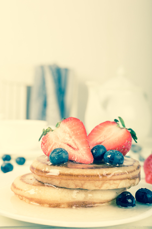 homemade style: Healthy breakfast concept. Homemade pancakes with strawberries, blueberries and honey. Retro style toned.