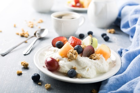 quark: Healthy breakfast, quark with granola, fruits and berries on light wooden background.