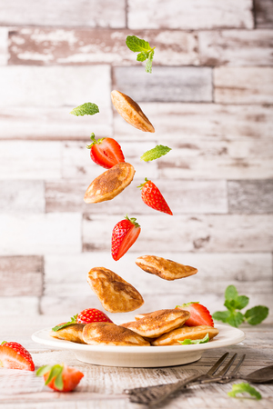 Plate with dutch mini pancakes called poffertjes with flying ingredients, pancakes, strawberries and mint, sprinkled with powdered sugar. Healthy food concept with copy space.