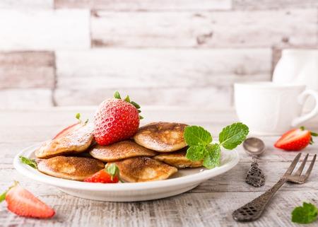 Nederlandse mini pannen koeken genoemd poffertjes met aardbeien en mint, bestrooid met poedersuiker. Gezond voedsel concept met een kopie ruimte.
