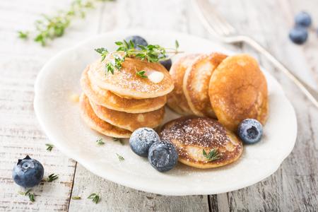 Nederlandse mini pannen koeken genoemd poffertjes met bosbessen en tijm, bestrooid met poedersuiker. Gezonde voeding concept.