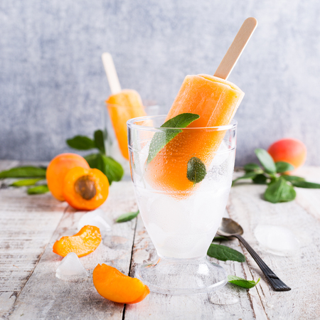 Homemade apricot popsicles in glass with ice and apricot fruits. Summer healty food concept. Stock Photo