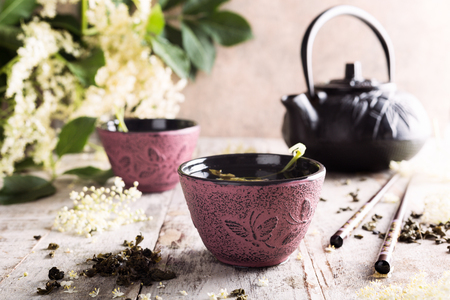 diuretic: Healthy medicine green tea with elder flower in pink cast iron cup on old white wooden table with elder flower branches. Copy space. Stock Photo
