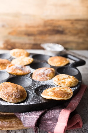 grooves: Homemade dutch mini pancakes called poffertjes on special pan with grooves. Healthy food concept with copy space.