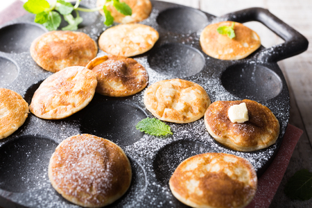 dutch: Homemade dutch mini pancakes called poffertjes with mint on special pan with grooves. Healthy food concept with copy space.