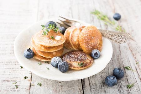 Mini crepes holandesas llamaron poffertjes con los arándanos y el tomillo, espolvoreadas con azúcar en polvo. Concepto de alimentos saludables. Foto de archivo - 59208510