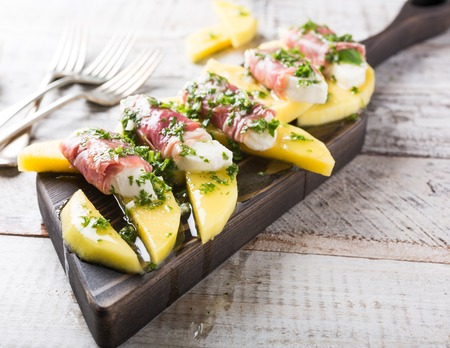parma ham: Rolls of mozzarella, basil and Parma ham on slices of mango with yoghurt sauce on wooden cutting board. Healthy eating concept with copy space