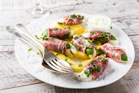 parma ham: Rolls of mozzarella, basil and Parma ham on slices of mango with yoghurt sauce on white plate. Healthy eating concept.