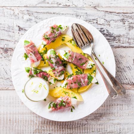 Rollos de mozzarella, albahaca y jamón de Parma sobre rebanadas de mango con salsa de yogur en un plato blanco. el concepto de alimentación saludable con espacio de copia Foto de archivo - 60399457