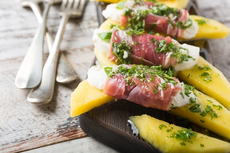 parma ham: Rolls of mozzarella, basil and Parma ham on slices of mango with yoghurt sauce on wooden cutting board. Healthy eating concept.