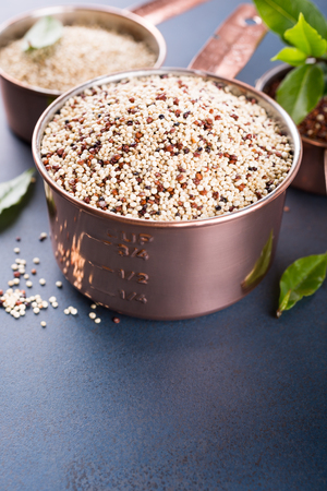 measuring cup: Mixed raw quinoa, South American grain, in copper measuring cups with bay laurel leaves on blue background. Healthy and gluten free food. Copy space. Stock Photo