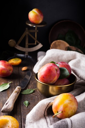 Fresh plums in bronze bowl on rustic wooden background. Selective focus. Healthy food concept.