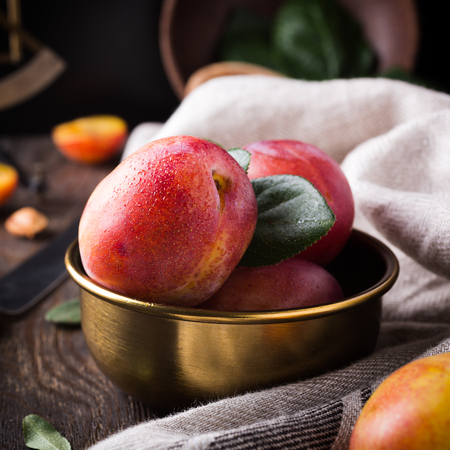 bronze bowl: Fresh plums in bronze bowl on rustic wooden background. Selective focus. Healthy food concept.