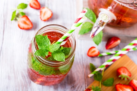 Homemade delicious strawberry compote in glass jar on white wooden table. Healthy food concept. View from above.