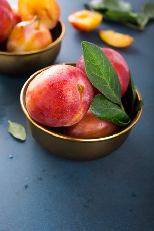 Fresh plums in bronze bowl on blue stone background. Selective focus. Healthy food concept. Copy space.