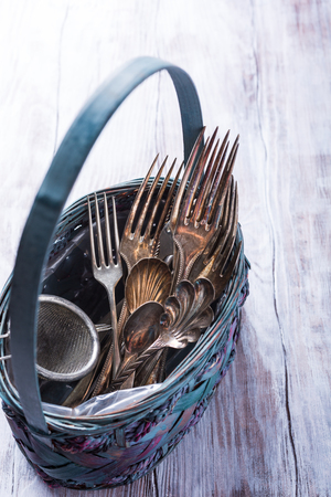 vintage cutlery: Vintage cutlery in old blue wicker basket on wooden rustic background