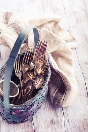 vintage cutlery: Vintage cutlery in old blue wicker basket on wooden rustic background. Retro style toned.