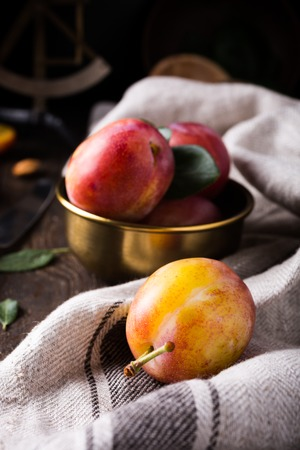 Fresh plums in bronze bowl on rustic wooden background. Selective focus. Healthy food concept. Focus on the front plum.
