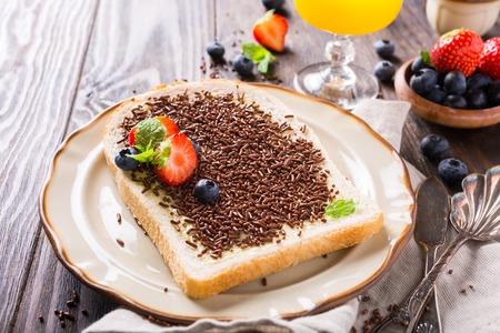 chocolate sprinkles: Dutch breakfast, slice of bread with hagelslag chocolate sprinkles and berries. Stock Photo