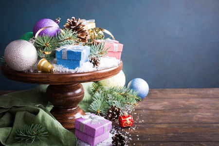 Christmas greeting card with gifts, christmas tree and snow on wooden cake stand. With copy space for text. Stock Photo