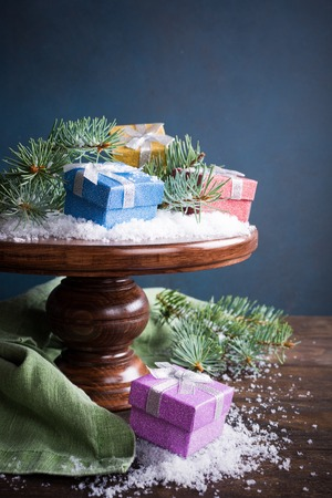 cake stand: Christmas greeting card with gifts, christmas tree and snow on wooden cake stand. With copy space for text. Stock Photo