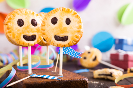 Homemade shortbread smile cookies with dark chocolate on stick called pie pops. Childrens party background. Stock Photo