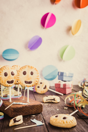 Homemade shortbread emoticon cookies with dark chocolate on stick called pie pops. Childrens party background. Retro style toned.