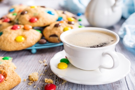 Cup coffee with homemade cookies with colorful chocolate candies on old white wooden table. 版權商用圖片