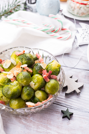 Brussels sprouts with fried bacon and almonds. Delicious Christmas themed dinner table. Holiday concept. Stock Photo