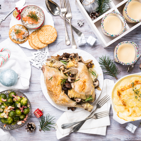 Delicious Christmas themed dinner table with roasted chicken, appetizers and desserts. Top view. Holiday concept. Stock Photo