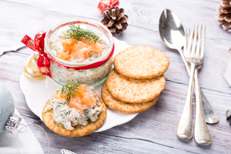 Smoked salmon, soft cheese and dill spread, mousse, pate, rillette in a jar with crackers on white wooden background. Delicious Christmas themed dinner table. Holiday concept. Stok Fotoğraf