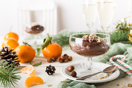 Chocolate pudding mousse with avocado, nuts and christmas decorations. Delicious Christmas themed dinner table. Stock Photo