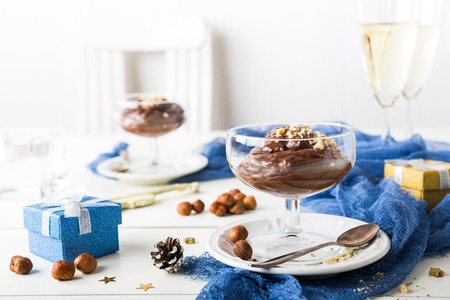 Chocolate pudding mousse with avocado, nuts and holiday decorations. Delicious Christmas themed dinner table. Stock Photo