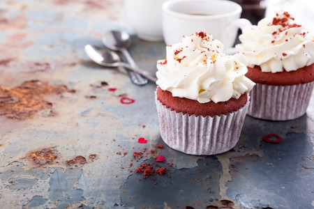 Delicious red velvet cupcakes for Valentines Day on rusty old metal background. Holiday food concept. Copy space. Stock Photo