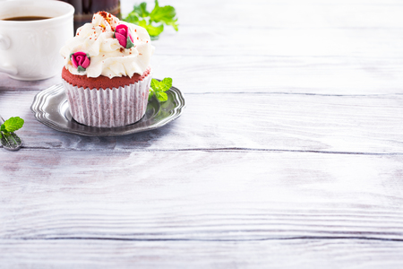 afternoon fancy cake: Dessert for Valentines Day, beautiful red velvet cupcake decorated with pink rose on old white wooden background with copy space. Stock Photo
