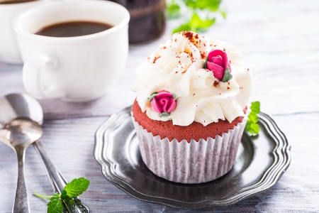 red velvet cupcake: Dessert for Valentines Day, beautiful red velvet cupcake decorated with pink rose on old white wooden background. Stock Photo