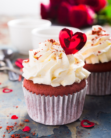 Delicious red velvet cupcakes decorated with hearts on rusty old metal background. Holiday food concept. Valentines Day.