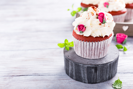 Delicious red velvet cupcakes decorated with pink rose on old white wooden background. Valentines Day dessert. Copy space. Stock Photo