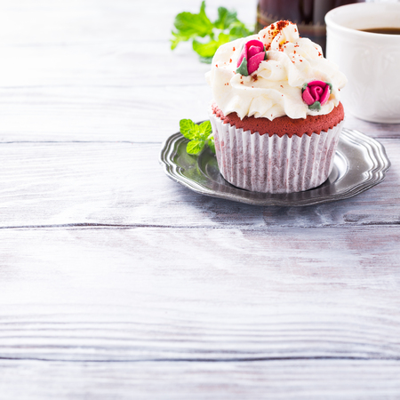 Dessert for Valentines Day, beautiful red velvet cupcake decorated with pink rose on old white wooden background with copy space. Stock Photo