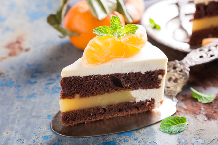 Piece of delicious chocolate cake with mandarin tangerine jam covered with cheese cream on old rusty blue metal background. Selective focus.