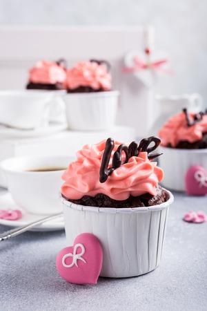 Beautiful chocolate cupcake, pink cream and heart on gray stone background. Valentines, Mother Day, wedding concept with with copy space.