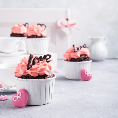 afternoon fancy cake: Beautiful chocolate cupcake, pink cream and heart on gray stone background. Valentines, Mother Day, wedding concept with with copy space.