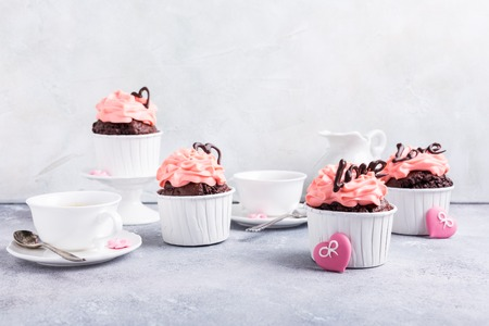 Beautiful chocolate cupcake, pink cream and heart on gray stone background. Valentines, Mother Day, wedding concept with copy space.