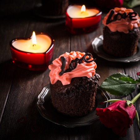 Beautiful chocolate cupcake with pink cream on wooden background. Valentines, Mother Day, wedding greeting card. Dark photo.
