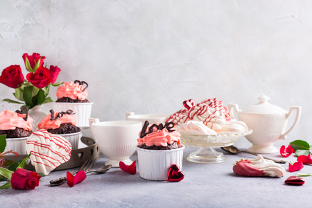 Beautiful chocolate cupcake, pink cream, meringue cookies and red roses on gray stone background. Valentines, Mother Day, wedding concept with with copy space.