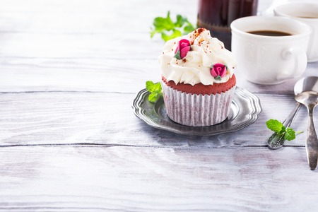 red velvet cupcake: Dessert for Valentines Day, beautiful red velvet cupcake decorated with pink rose on old white wooden background with copy space. Stock Photo