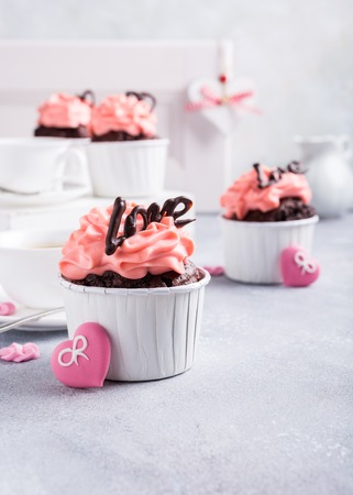 afternoon fancy cake: Valentines and Mother Day, wedding greeting card with beautiful chocolate cupcake, pink cream and heart on gray stone background with copy space.