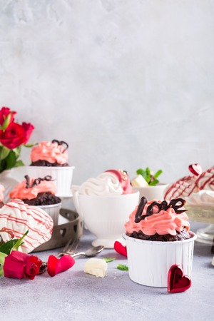 afternoon fancy cake: Beautiful chocolate cupcake, pink cream, meringue cookies and red roses on gray stone background. Valentines, Mother Day, wedding concept with copy space.