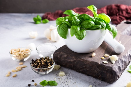 Ingredients for making green pesto sauce. Basil in white mortar on wooden cutting board. Healthy italian food.