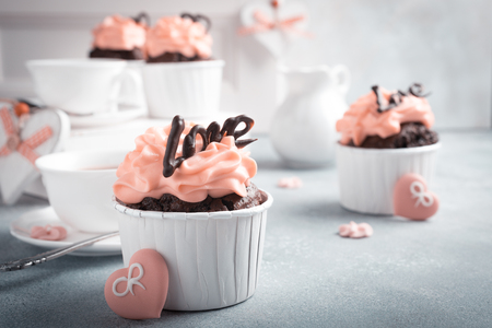 Beautiful chocolate cupcake, pink cream and heart on gray stone background. Valentines, Mother Day, wedding concept with copy space. Retro style toned.